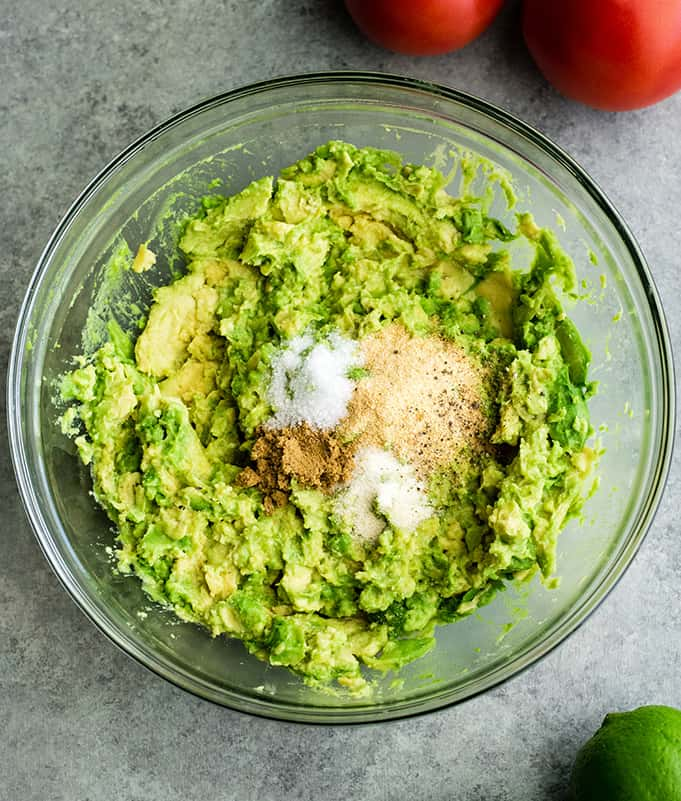 overhead view of the spices being added to mashed avocado in a glass bowl to make easy guacamole recipe