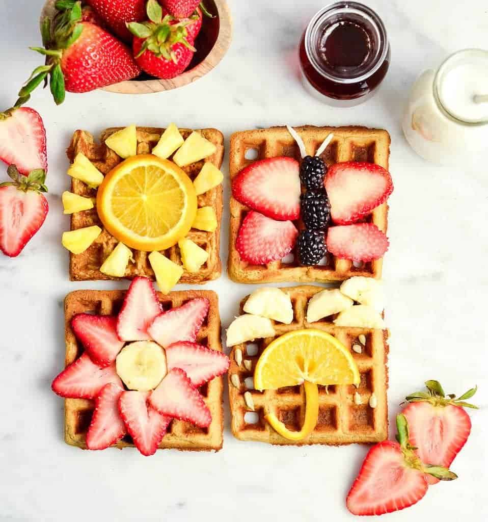 overhead view of four Peanut Butter Oatmeal Waffles with fun fruit designs on them