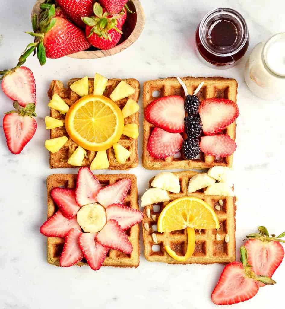 Overhead view of four Blender Peanut Butter Oatmeal Waffles with fun fruit designs on each one