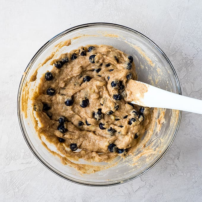 overhead view of a glass bowl showing the blueberries being mixed into the paleo blueberry muffin batter with a white spatula
