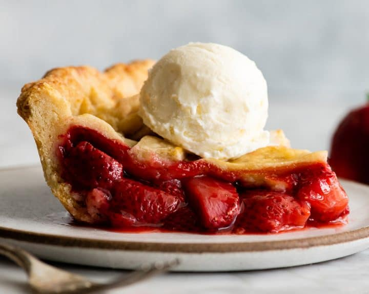 side view of a slice of strawberry pie with a scoop of ice cream on top