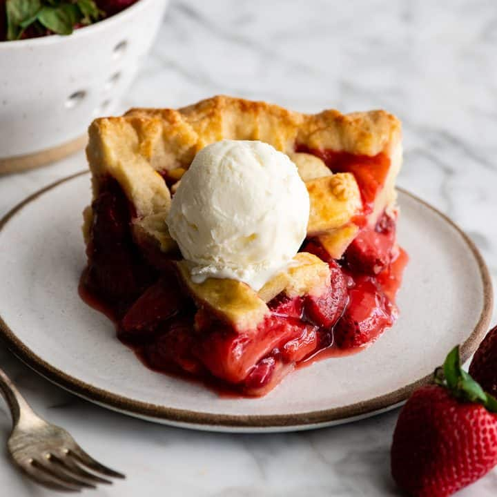 slice of strawberry pie on a plate with a scoop of ice cream on top