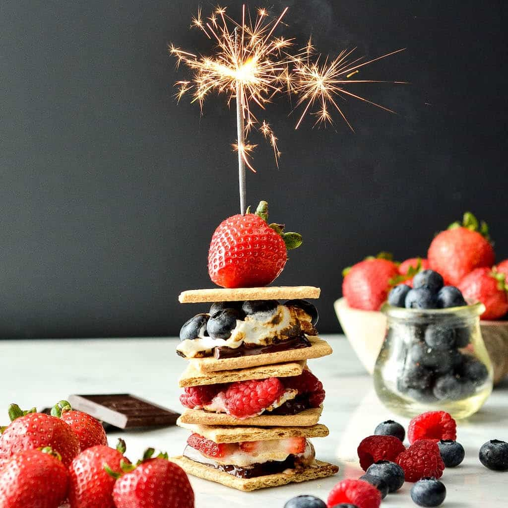 front view of a stack of three Dark Chocolate S'mores with Fresh Berries with a sparkler lit on top