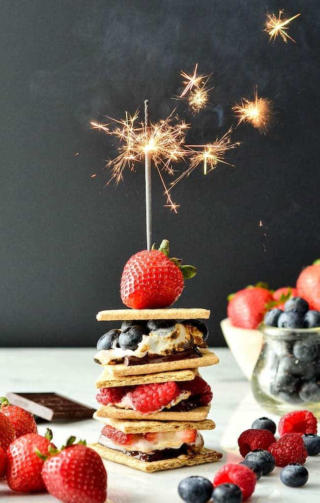 front view of a stack of three Dark Chocolate S'mores with Fresh Berries with a sparkler on top