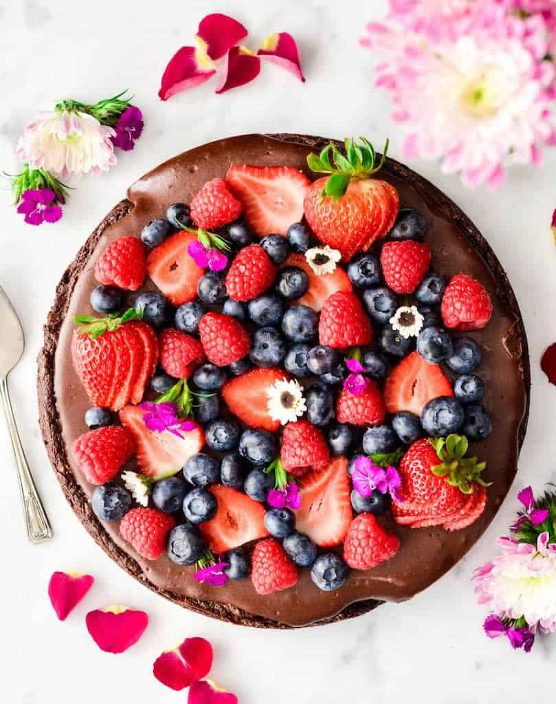 This Paleo Chocolate Fruit Pizza with a Brownie Cookie Crust is a decadent yet healthy dessert recipe. A layer of silky-smooth chocolate topping is slathered over an irresistibly chocolatey crust that's a cross between a brownie and a cookie, and topped with fresh berries. It's gluten-free & dairy-free and has no refined sugar but no one would ever guess that is' good for you!