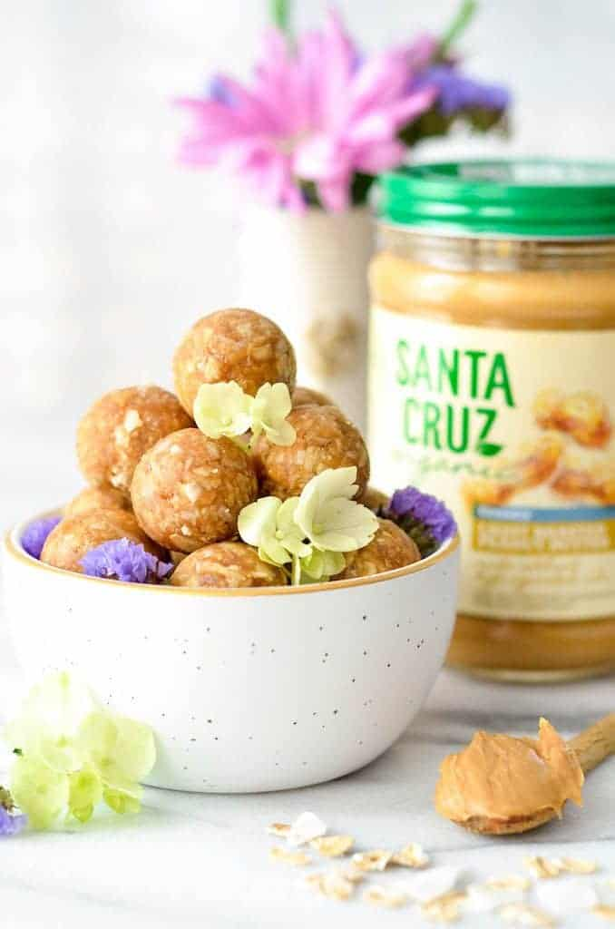 Side view of a bowl of Peanut Butter Oatmeal Balls with peanut butter and flowers in the background