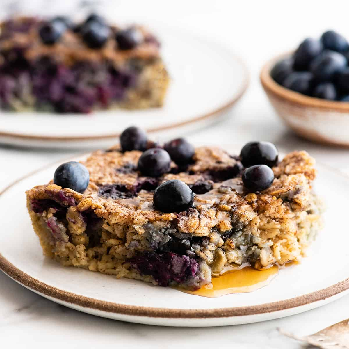 front view of a piece of blueberry baked oatmeal on a plate