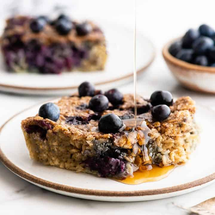 front view of syrup being poured onto a piece of Blueberry Baked Oatmeal on a plate
