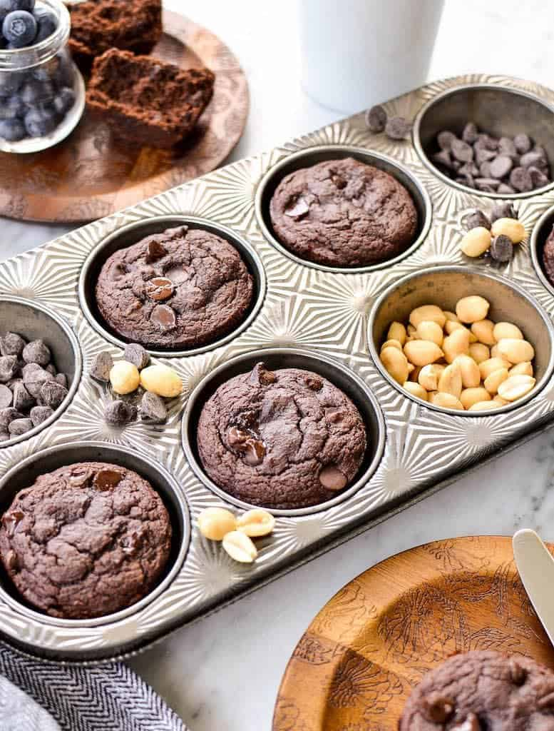 Side view of Peanut Butter Chocolate Zucchini Muffins in a muffin tin surrounded by peanuts and chocolate chips