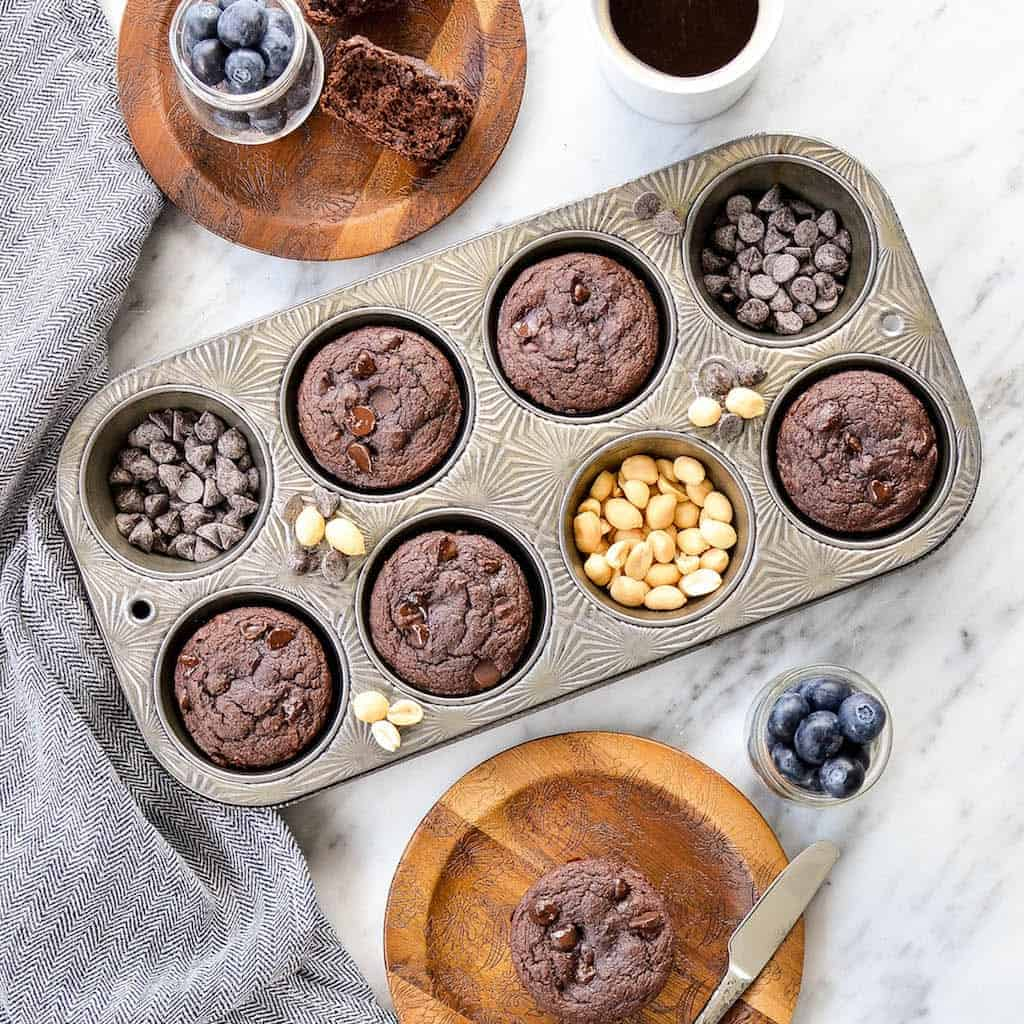 Overhead view of Peanut Butter Chocolate Zucchini Muffins in a muffin tin with two muffins on plates next ot the tin