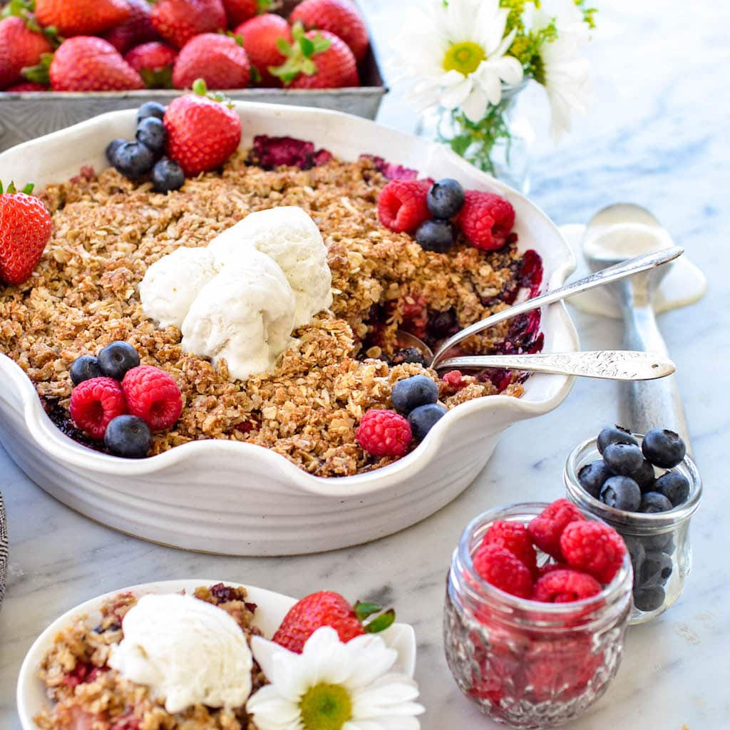 This Healthy Berry Crisp with a Coconut Oat Crumb Topping is a delicious summer dessert recipe! It's vegan, gluten-free, dairy-free and has no refined sugar but no one would ever guess that it's healthy!