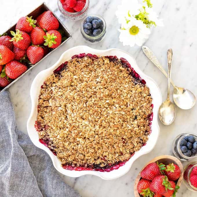 Overhead view of Healthy Berry Crisp Recipe in a pie dish surrounded by berries