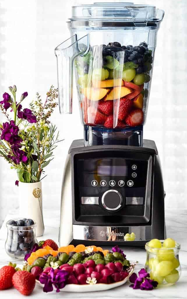 font view of a plate of Homemade Fruit Snacks recipe arranged by color in front of a vitamix blender filled with fruit