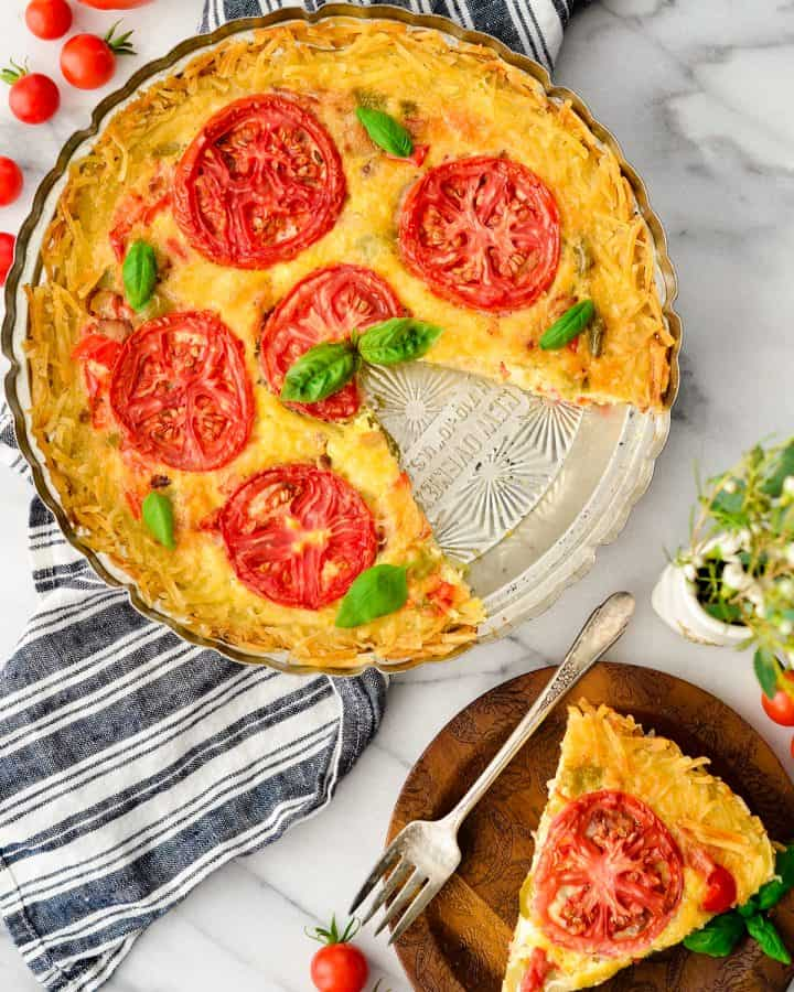 Overhead view of Gluten-Free Hash Brown Quiche with one slice cut out and on a plate next to it