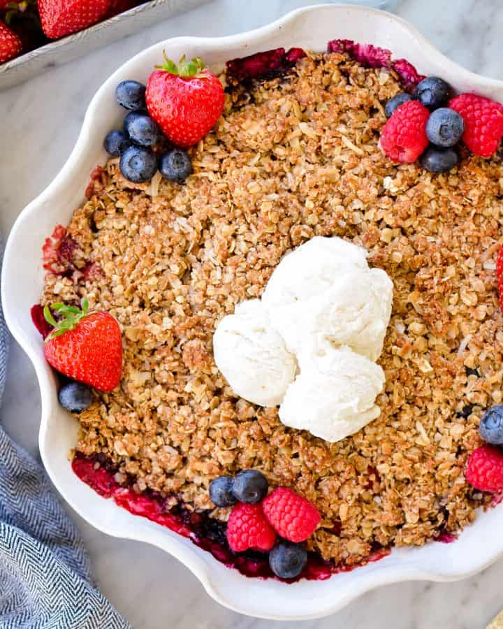 Overhead view of Healthy Berry Crisp Recipe garnished with fresh berries and vanilla ice cream