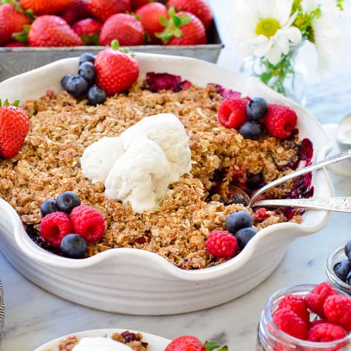 Side view of a pie dish of Healthy Berry Crisp with two spoons in it
