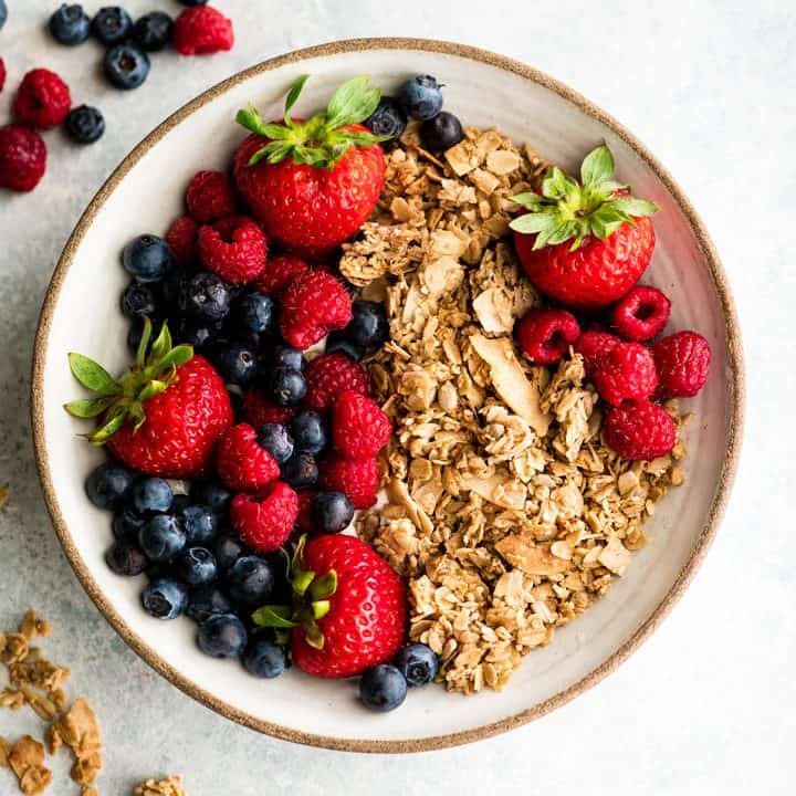 overhead view of a bowl of healthy homemade granola with berries