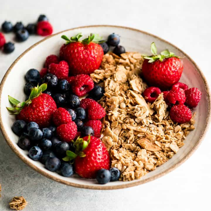 front view of a bowl of homemade granola recipe with berries