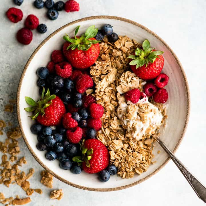 a bowl of healthy homemade granola over yogurt with berries and a spoon taking a bite out of it
