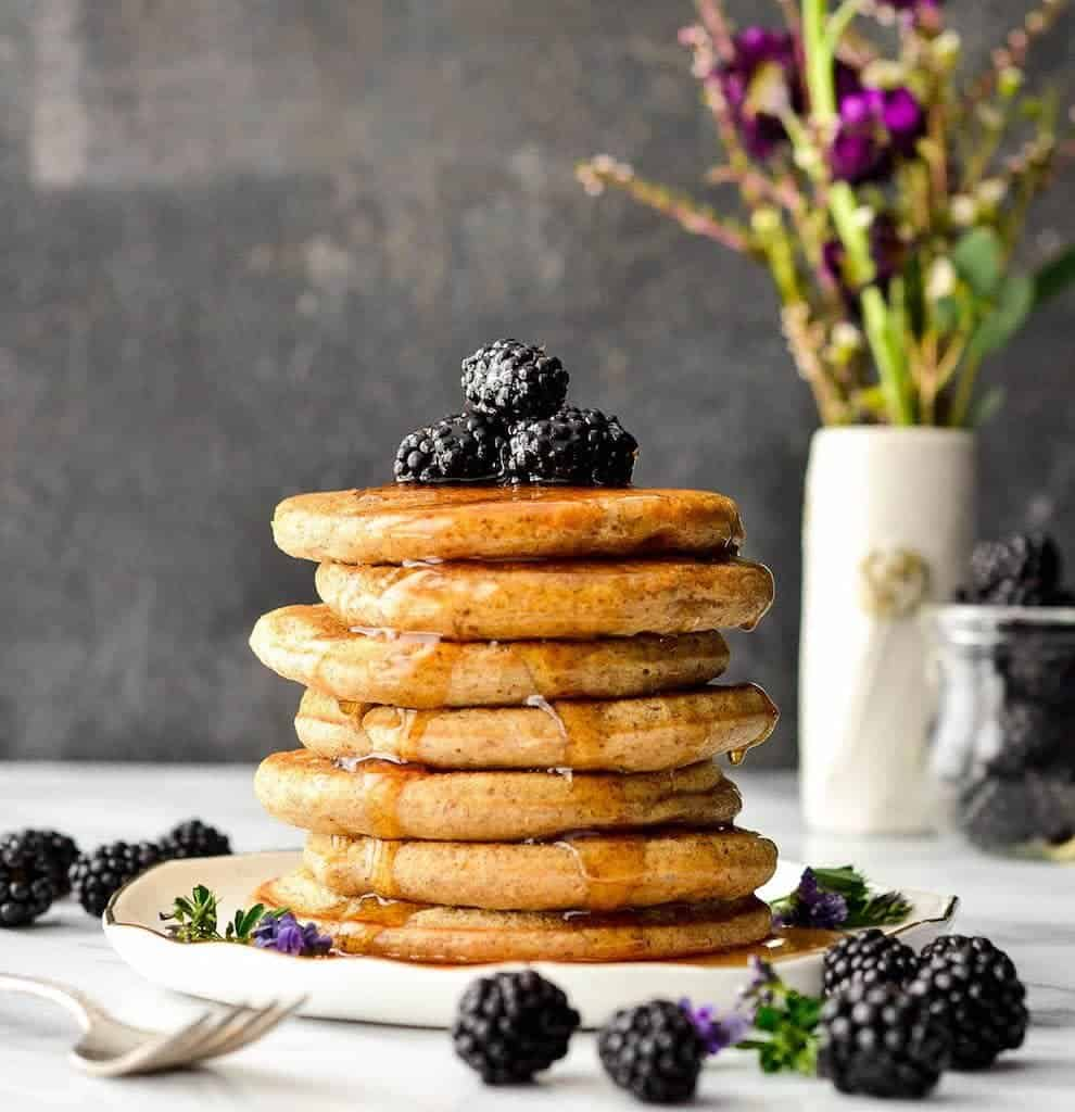Stack of seven Fluffy Whole Wheat Pancakes covered in maple syrup
