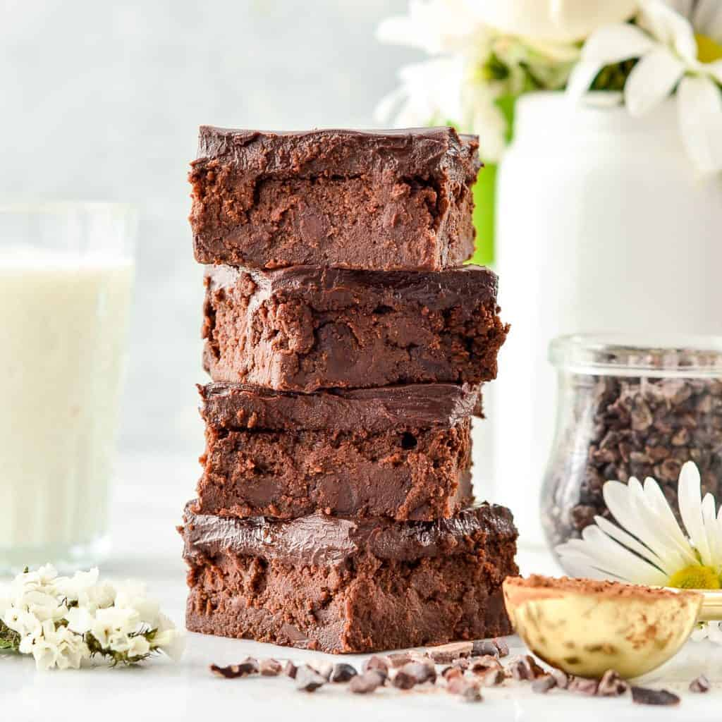 Front view of a stack of four fudgy healthy Greek Yogurt Browneis with flowers.