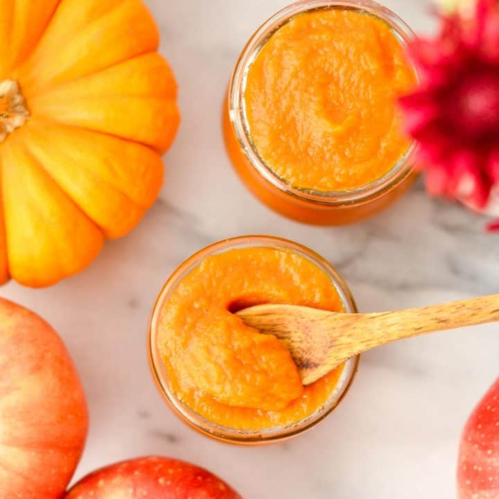 Overhead view of a spoon scooping out some Homemade Apple & Pumpkin Baby Food from a glass jar