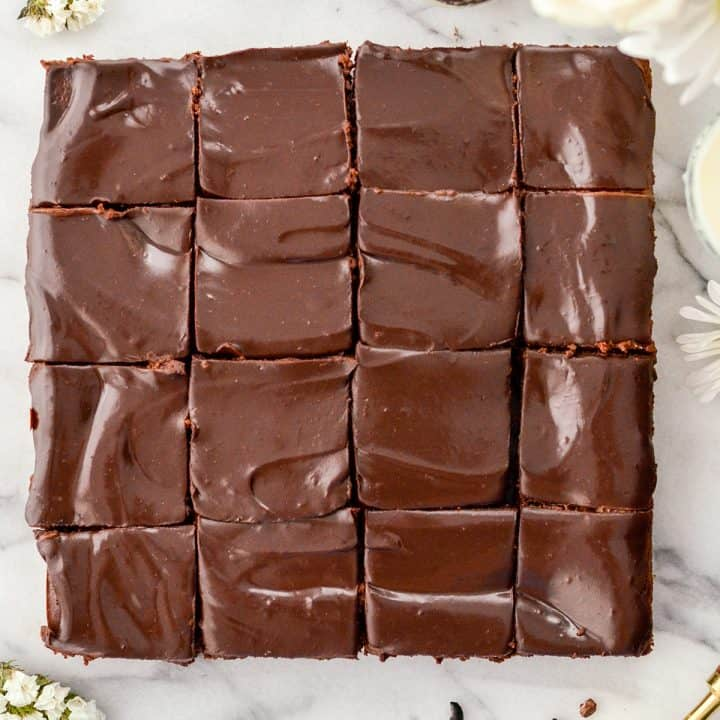 Overhead view of Healthy Greek Yogurt brownies cut into 16 square pieces. A shiny chocolate ganache with swirls.