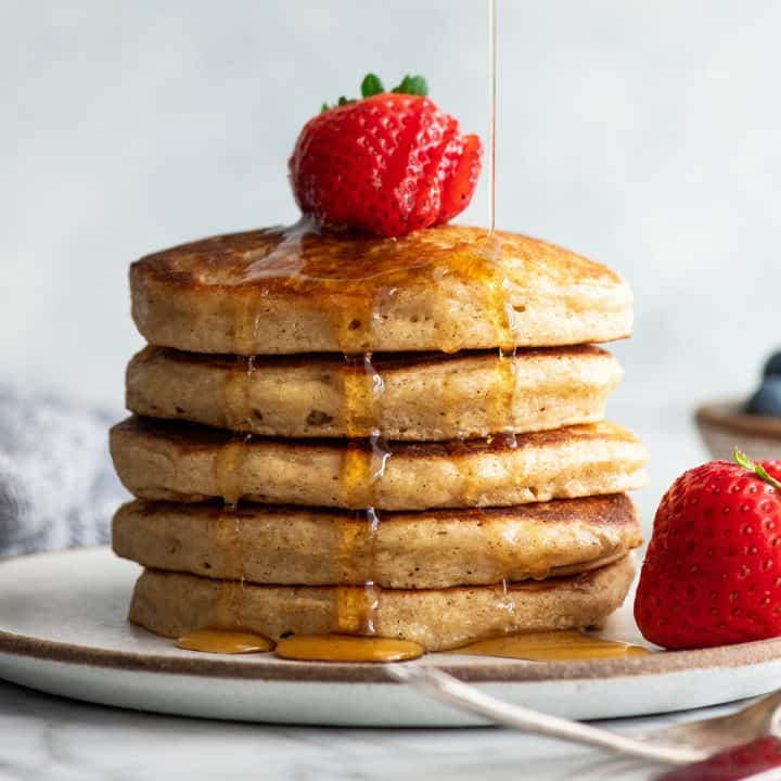 front view of a stack of 5 whole wheat pancakes with syrup pouring on them