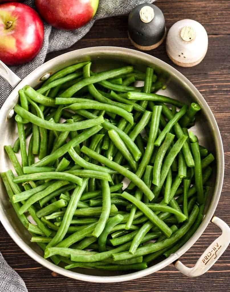 Overhead view of Sautéed Green Beans Recipe in a frying pan before cooking