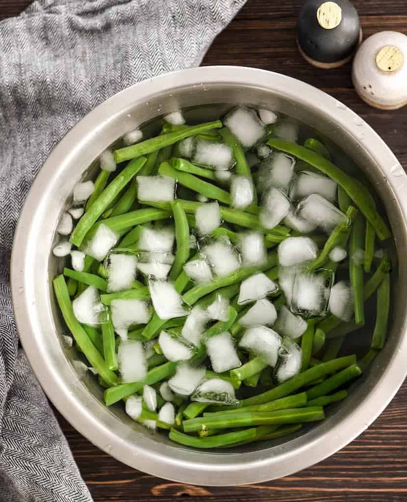 Overhead view of a bowl of fresh green beans in ice water to show how to cook fresh green beans by blanching