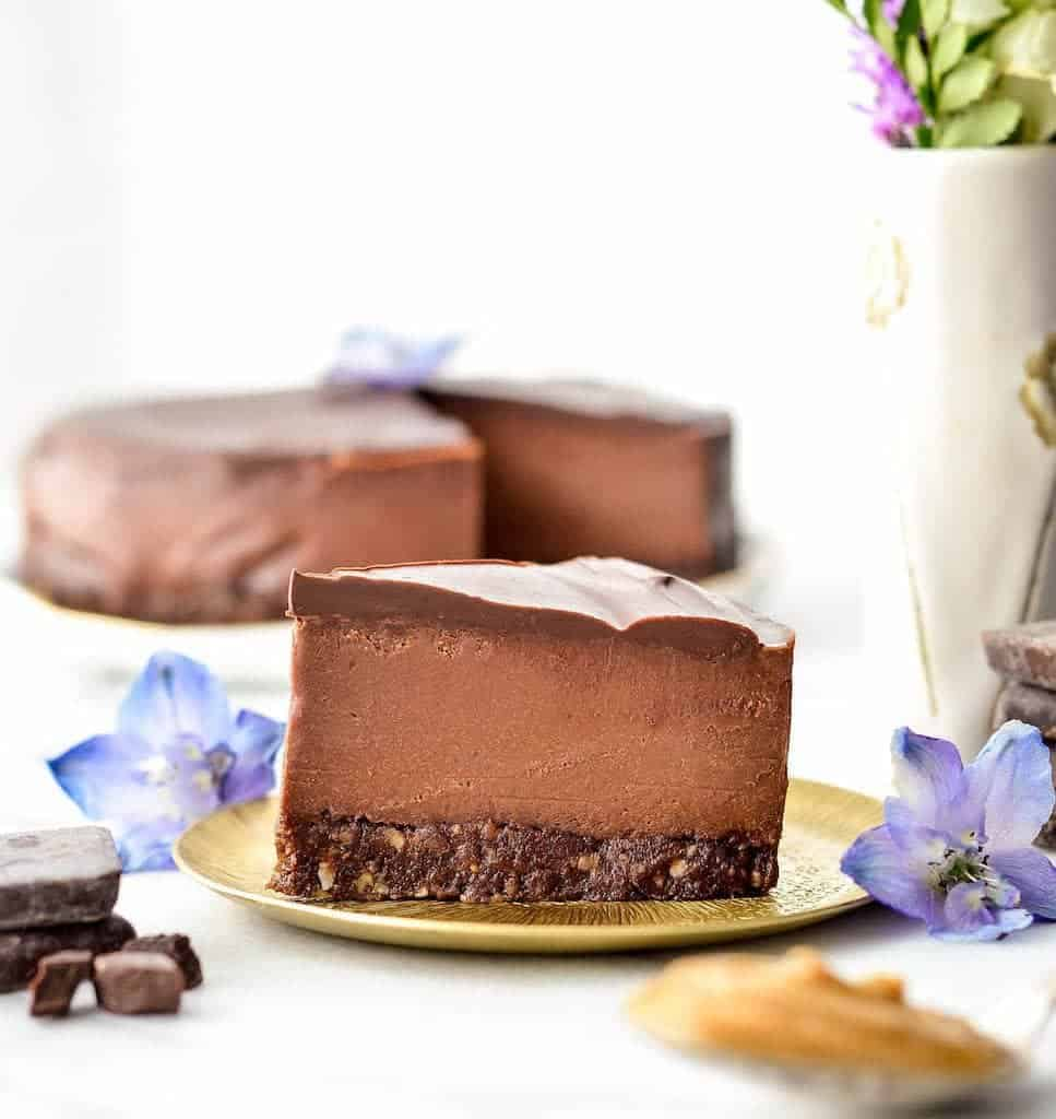 Side view of a slice of No-Bake Vegan Chocolate Peanut Butter Cheesecake on a plate with the rest of the cheesecake in the background