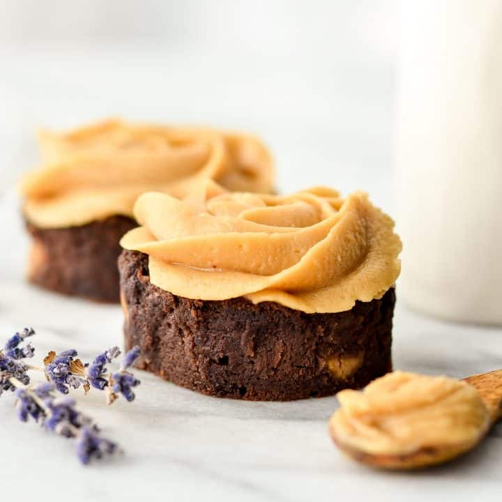Side view of two brownies frosting with homemade vegan peanut butter frosting piped on in the shape of a rose