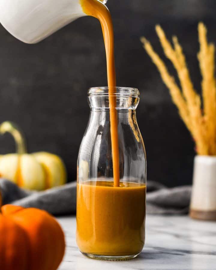 Front view of Pumpkin Coffee Creamer being poured into a glass bottle for storing