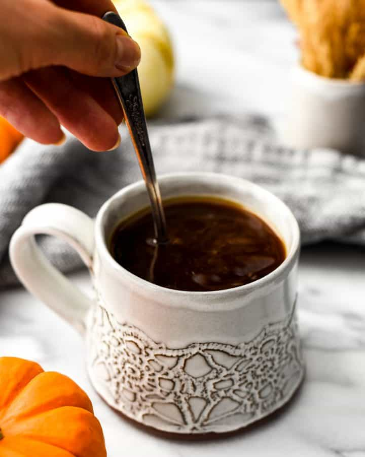 Hand holding a spoon stirring Homemade Pumpkin Coffee Creamer into a cup of coffee