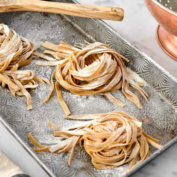 homemade whole wheat pasta before cooking covered in flour on a baking sheet