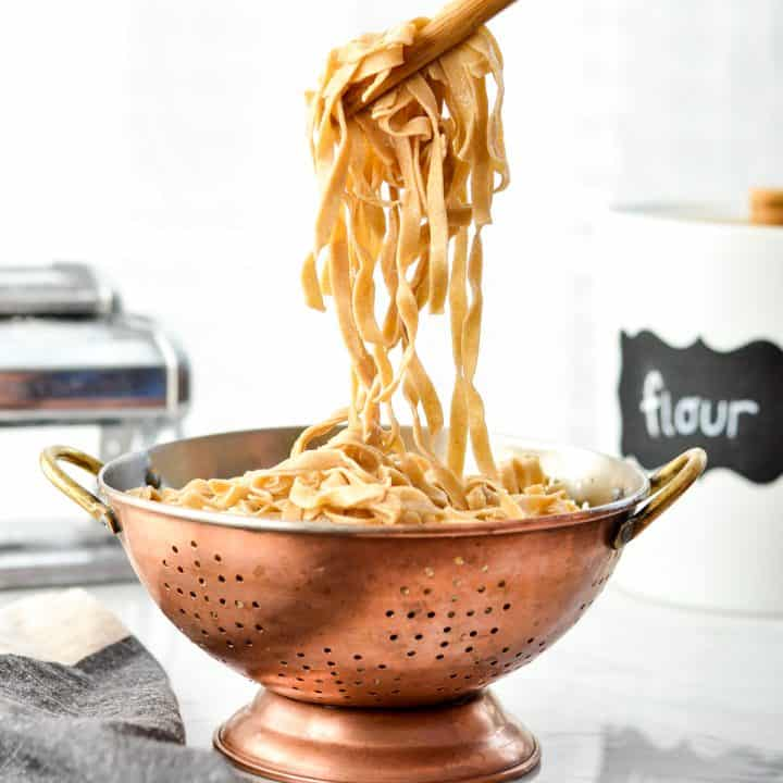 Front view of cooked Homemade Whole Wheat Pasta being pulled out of a colander with wooden tongs