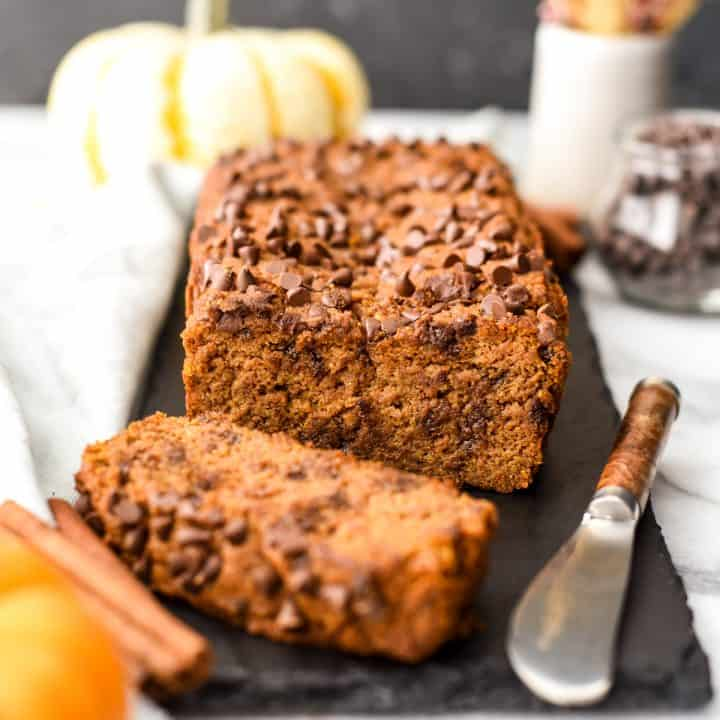 a loaf of chocolate chip paleo pumpkin bread with one slice cut out of it