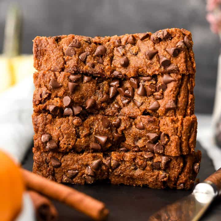 front view of a stack of four thick slices of paleo pumpkin bread with chocolate chips