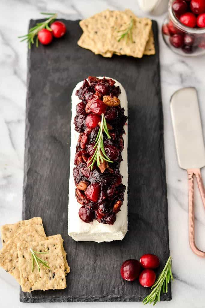 overhead view of Balsamic, Maple & Cranberry Goat Cheese Appetizer with Cinnamon Toasted Pecans on a cheese board with crackers
