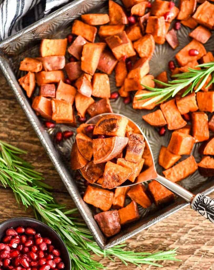 Overhead view of a pan of Cinnamon Roasted Sweet Potatoes with a spoon taking a scoop