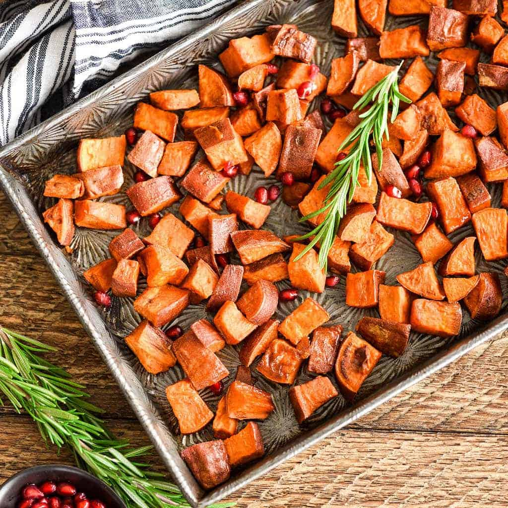 Overhead view of Maple Cinnamon Roasted Sweet Potatoes garnished with rosemary and pomegranate seeds