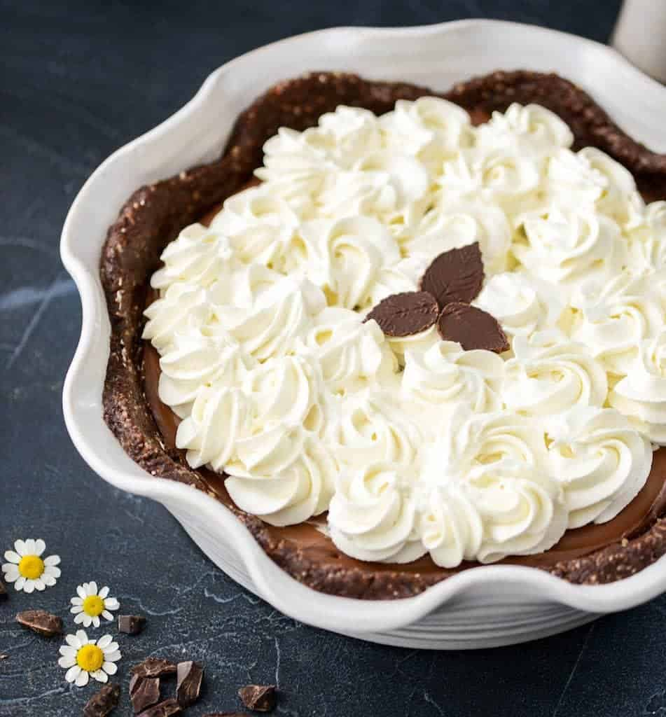 Overhead/side view of No-Bake Healthy Vegan Chocolate Pie with whipped cream roses and chocolate leaves
