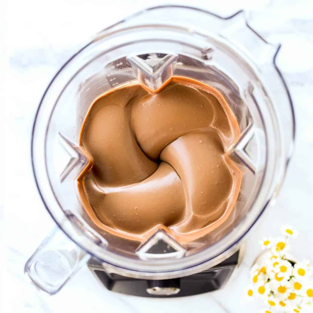 Overhead view of a chocolate vortex in a Vitamix which is the filling of No-Bake Healthy Vegan Chocolate Pie being made