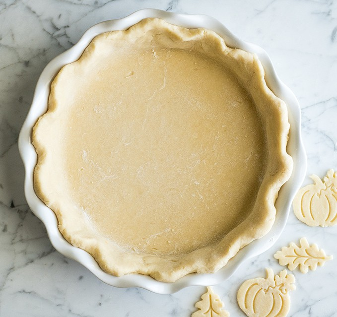 overhead view of a pumpkin pie crust shaped into the pie plate