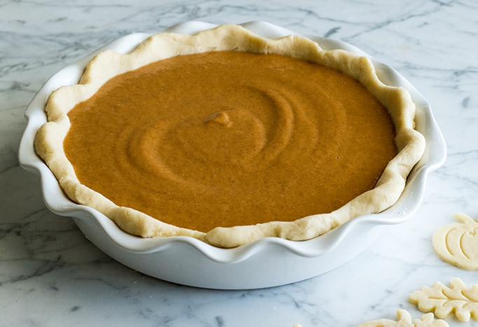 front view of the best pumpkin pie recipe in a white pie dish before baking