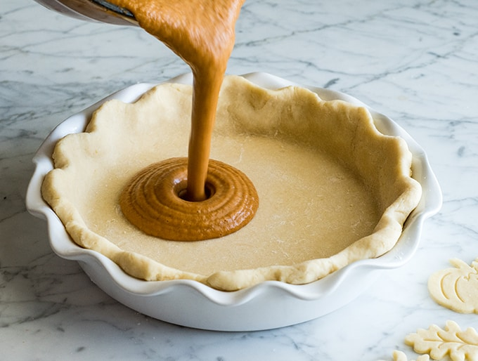 front view of pumpkin pie filling being poured into the crust to make the best pumpkin pie recipe