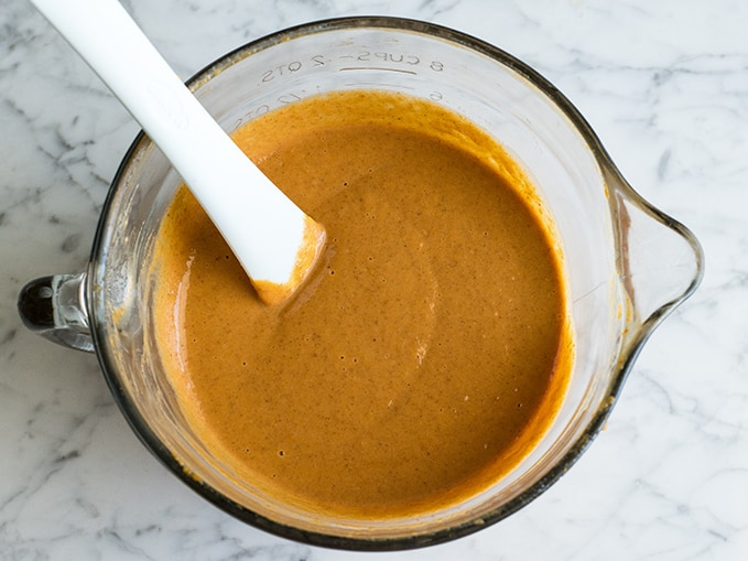 overhead view of the pumpkin pie filling in a glass bowl with a spatula