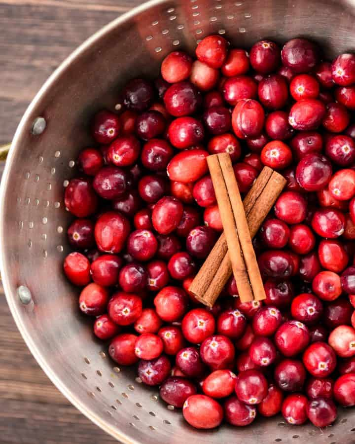 Overhead view of a colander with fresh cranberries and cinnamon sticks in it in the making of Healthy Cranberry Sauce