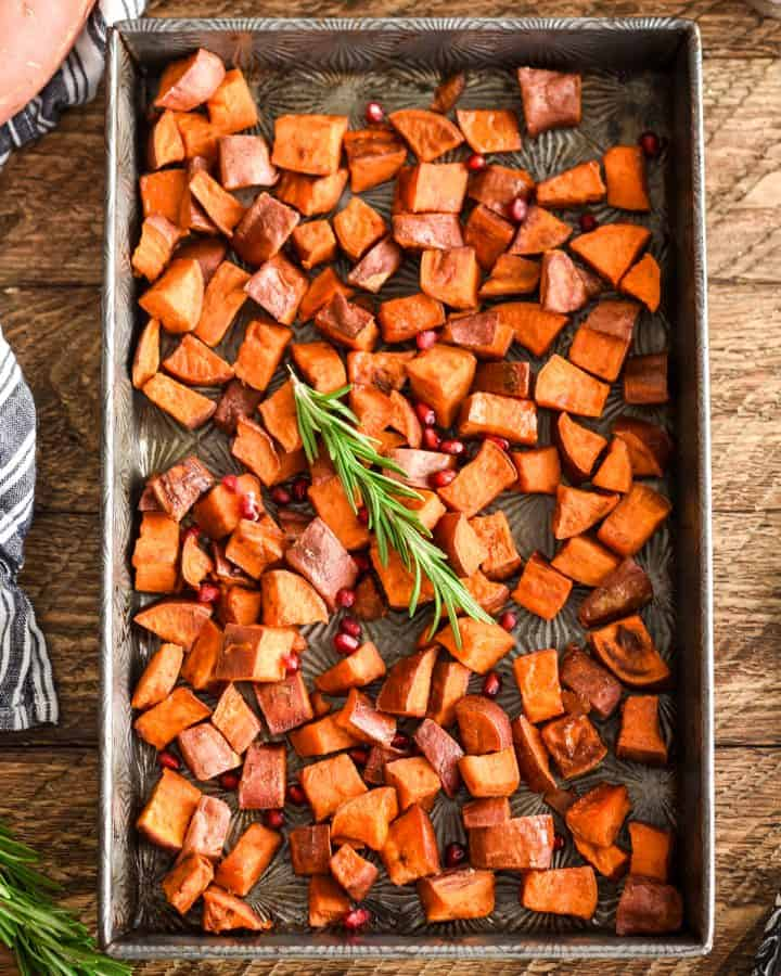 overhead view of a baking pan with Cinnamon Roasted Sweet Potatoes garnished with rosemary and pomegranate seeds