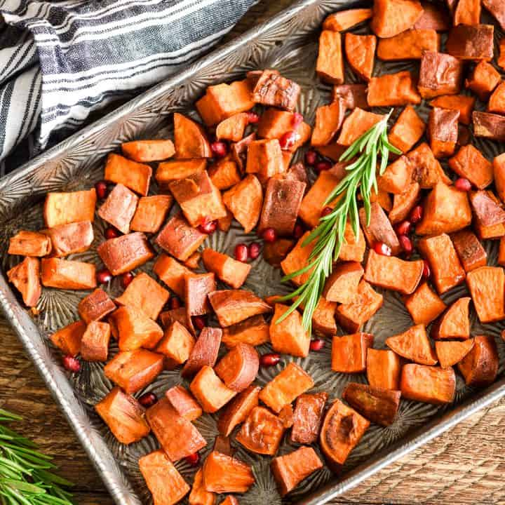 Overhead view of Cinnamon Roasted Sweet Potatoes garnished with rosemary and pomegranate seeds